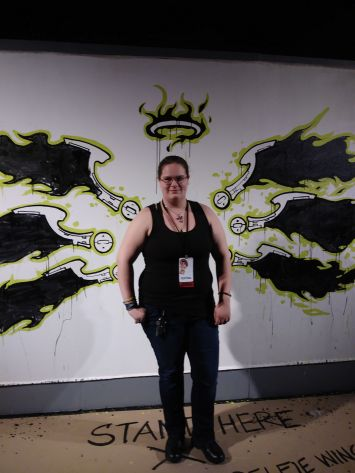 Zoe Brook stands in front of a mural of six green, black, and white stylized wings and a flaming green, black, and white crown.